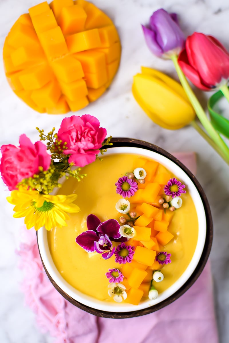 Springtime Mango Smoothie Bowl with Edible Flowers by Emily Kyle Nutrition