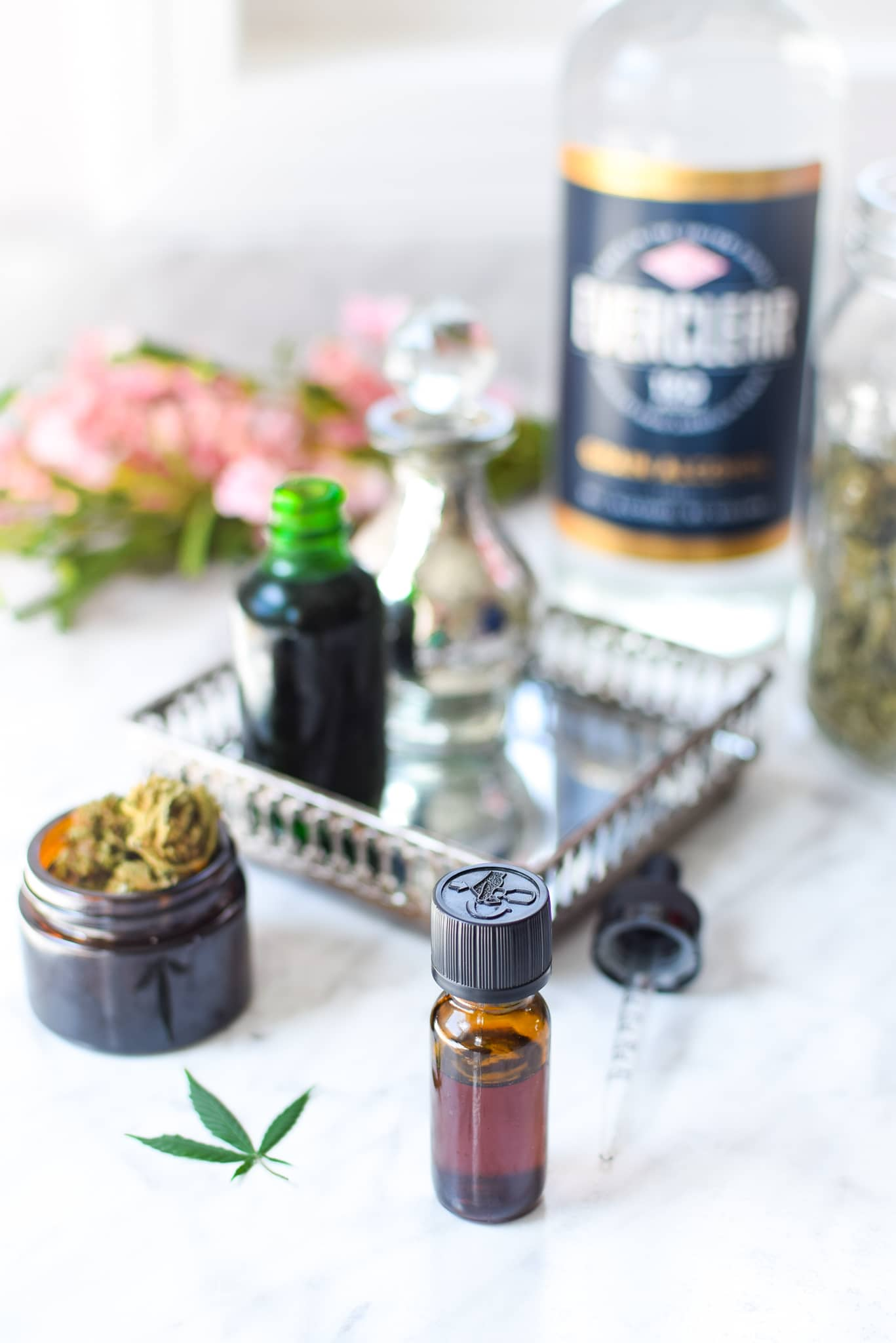 A white countertop with a metal tray with a amber tincture bottle with cannabis to the lefthand side, ever clear bottle in the background