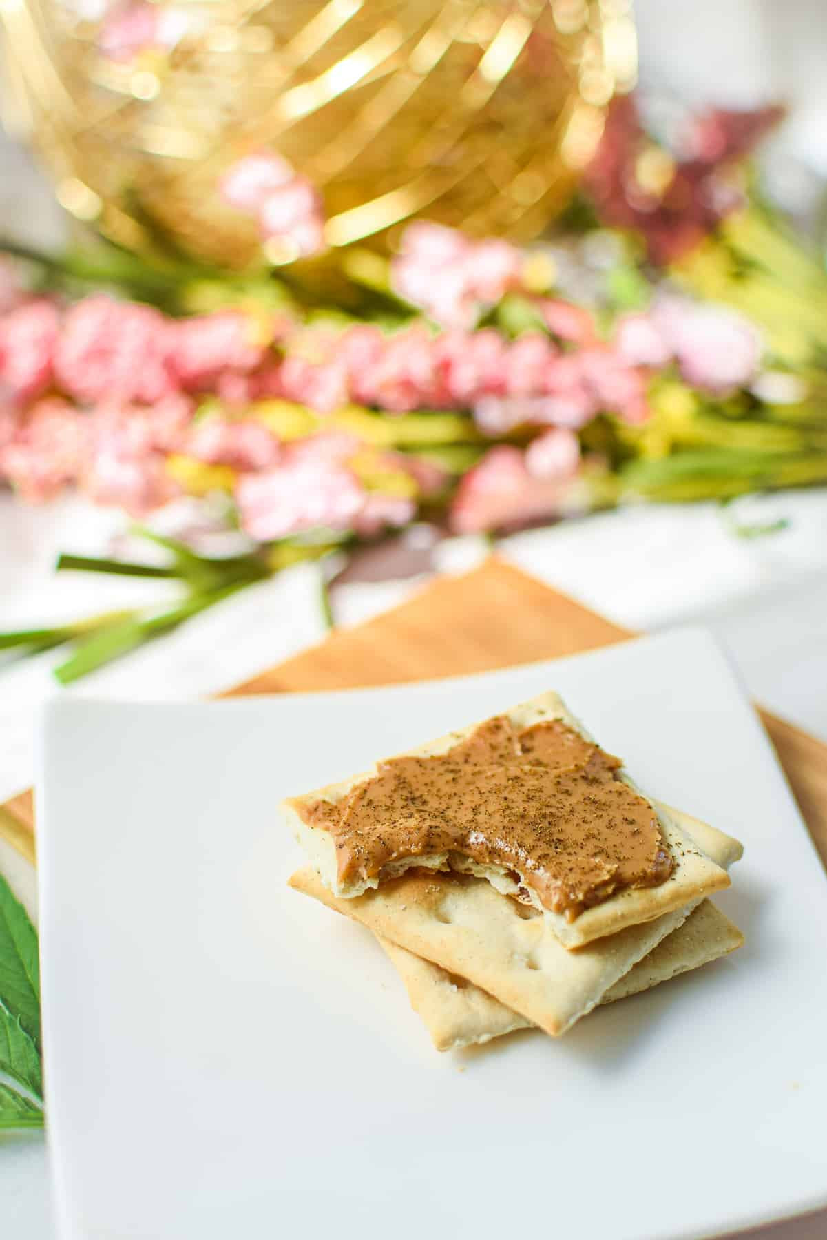 A picture of cannabis firecrackers, peanut butter and cannabis on top of a saltine cracker