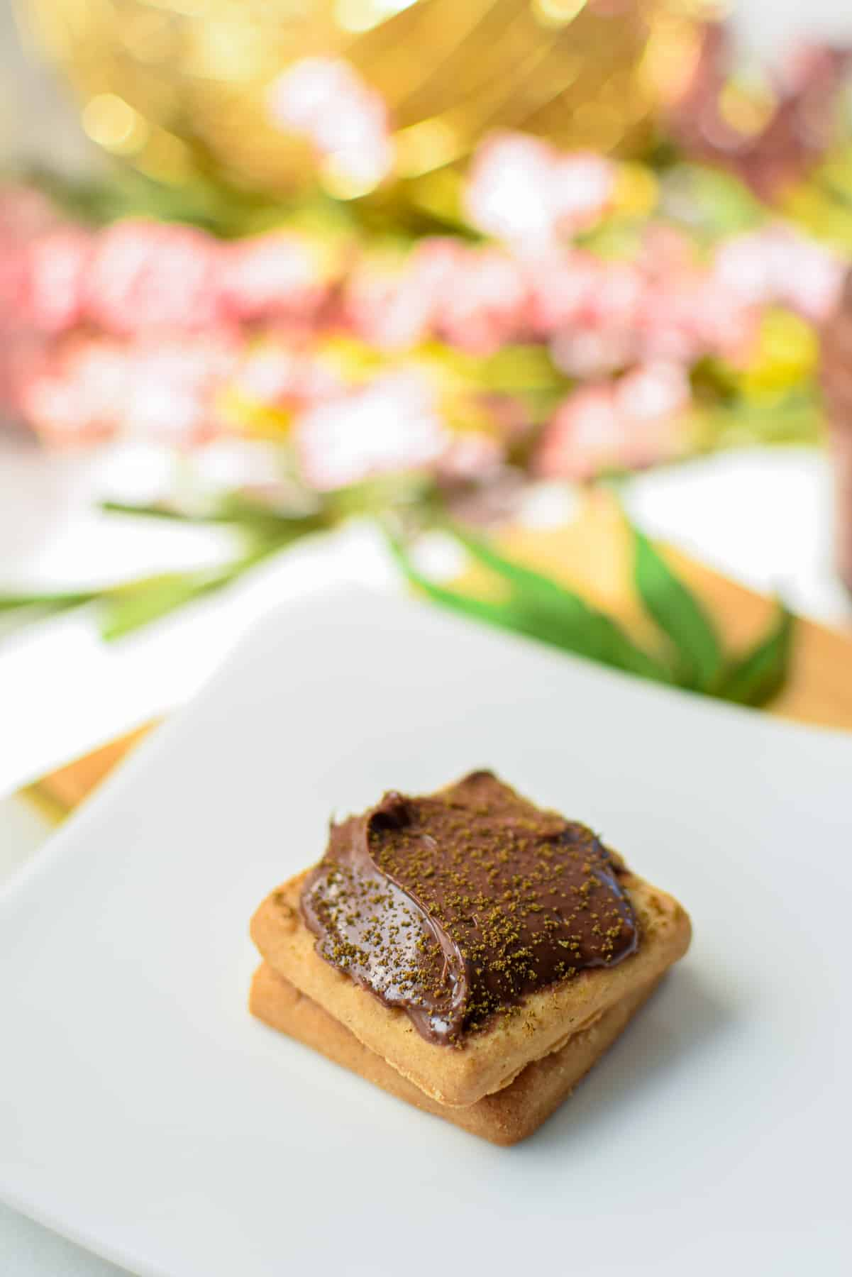 Small square cookies topped with Nutella topped with decarbed cannabis on a white plate.