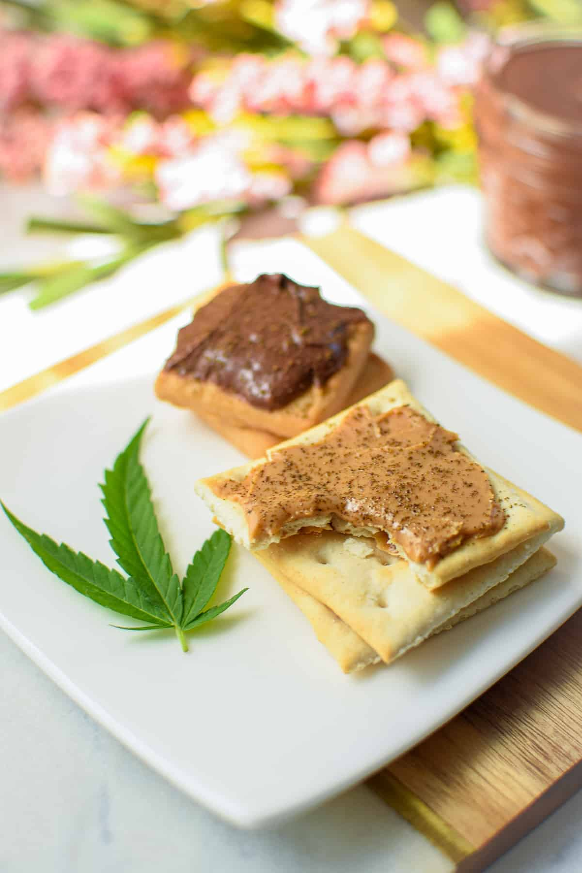 Saltine crackers topped with peanut butter and cannabis and cookies topped with Nutella and cannabis