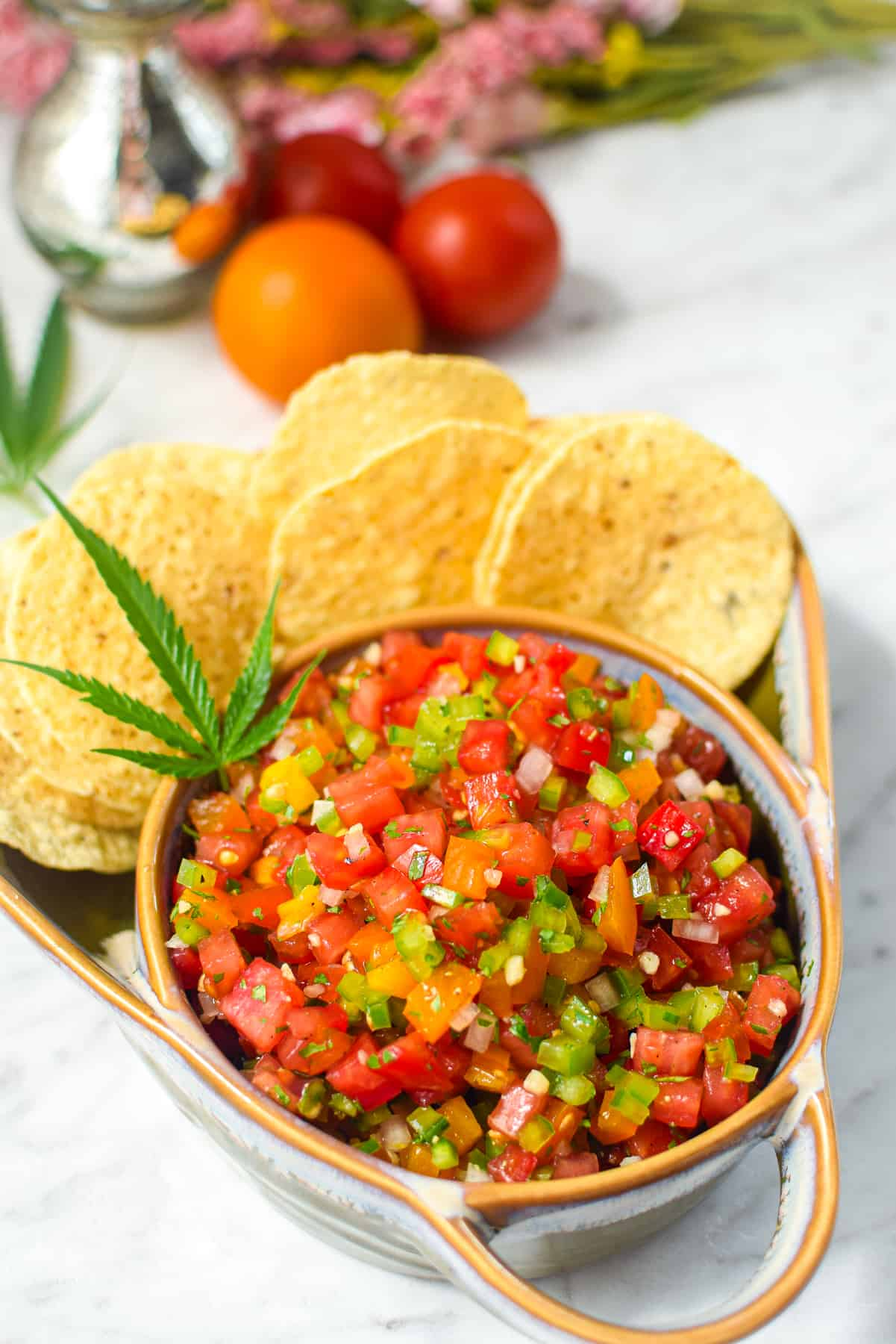 A finished bowl of cannabis infused salsa garnished with a cannabis fan leaf