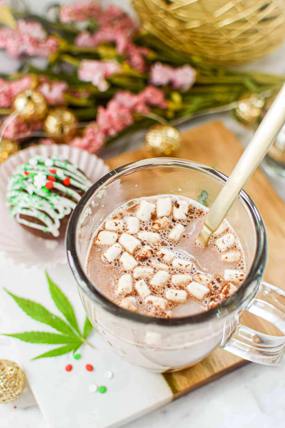 A white countertop with a cutting board topped with a clear mug full of milk and a hot cocoa bomb that has released cocoa mix and marshmallows
