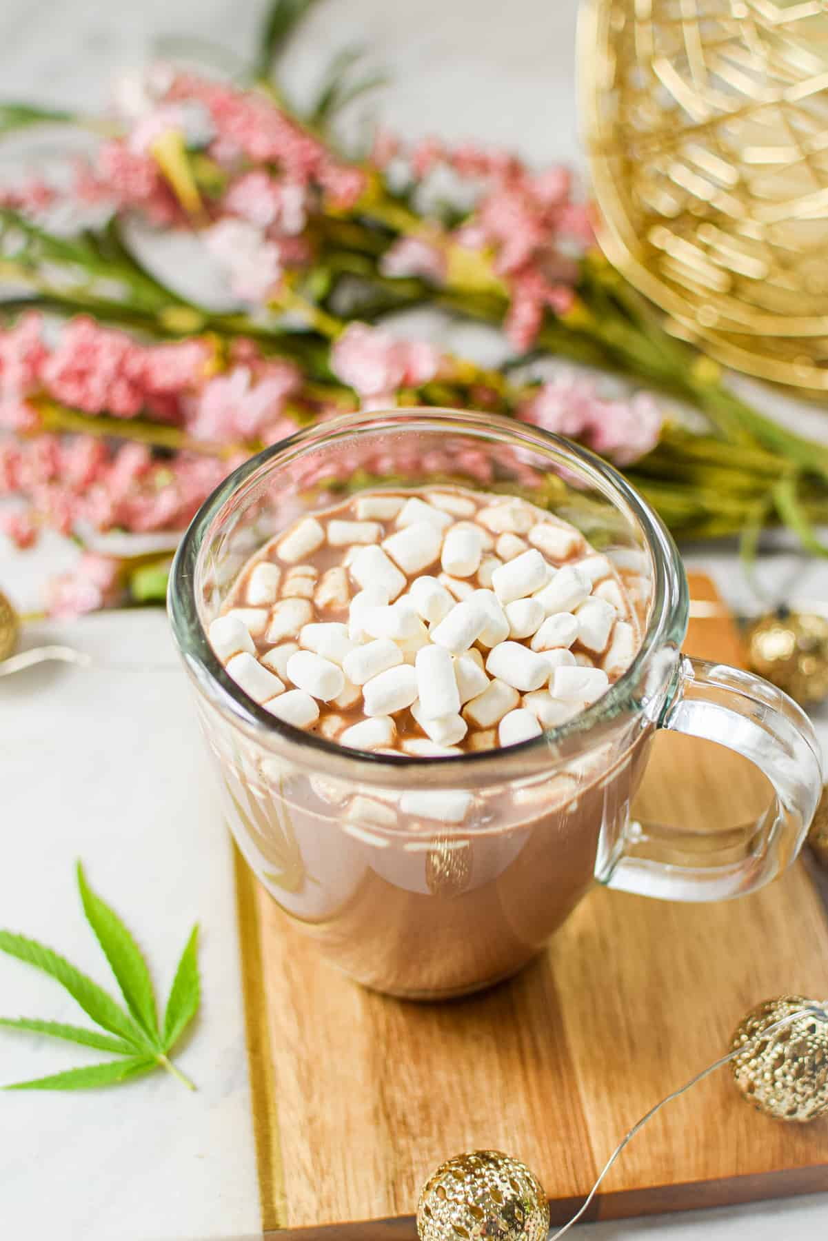 A white countertop with a cutting board topped with a clear mug full of cannabis hot cocoa with marshmallows