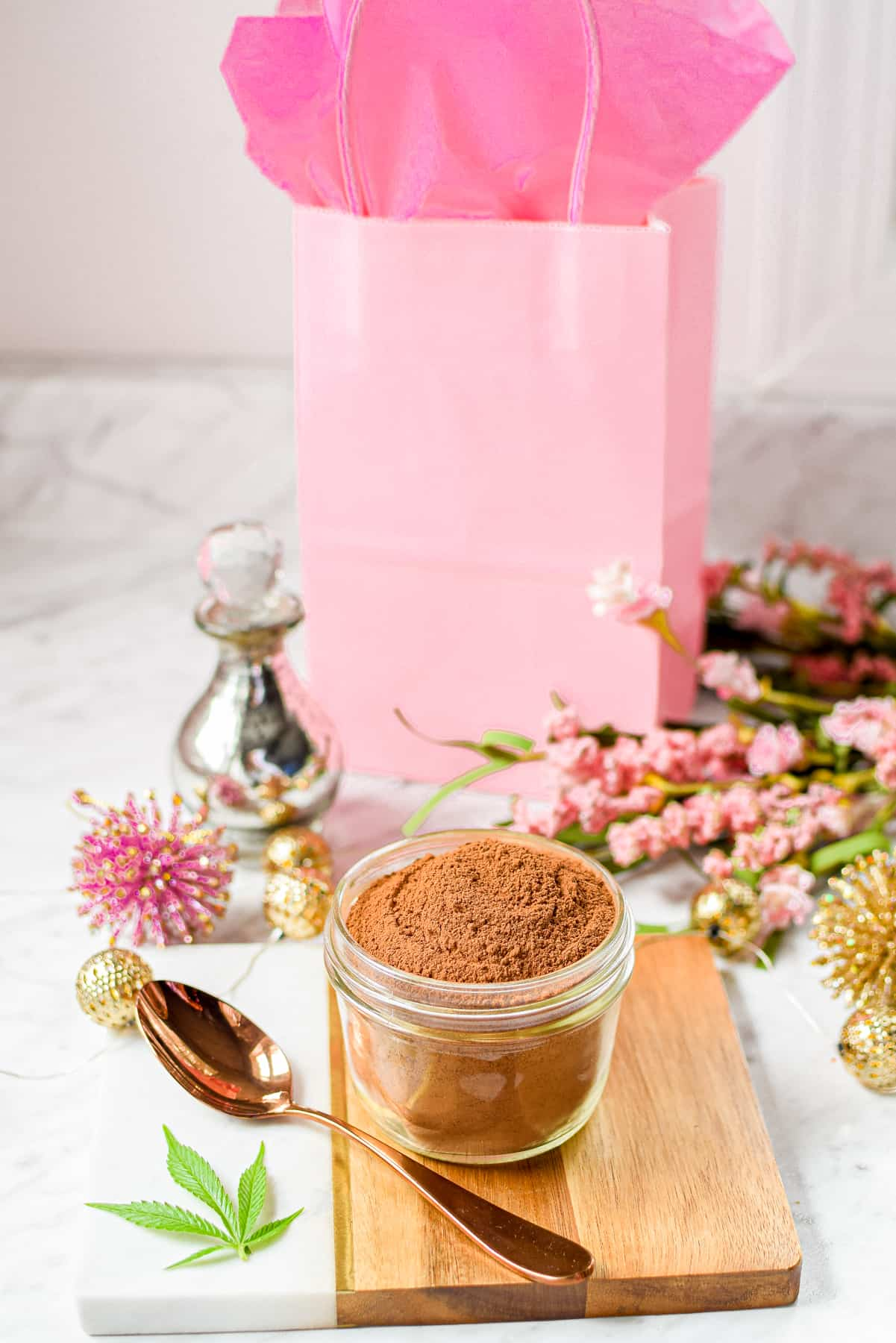 A white countertop with a cutting board topped with a glass mason jar filled with hot cocoa, with a pink gift back in the back of the photo.