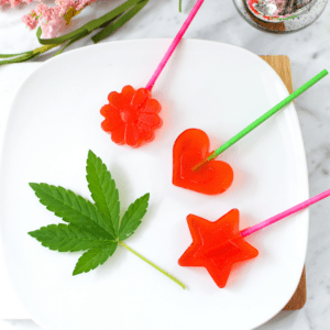A white plate with 3 red cannabis lollipops laying on it with a cannabis leaf on the left side for garnish