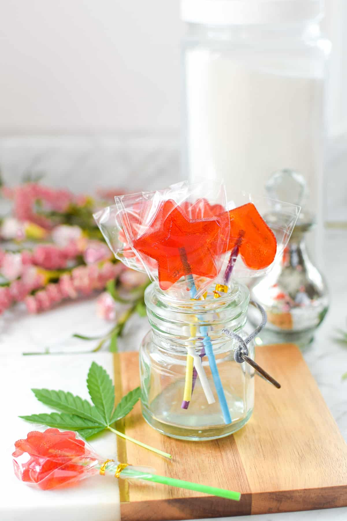 A wooden cutting board with a small mason jar full of red cannabis lollipops