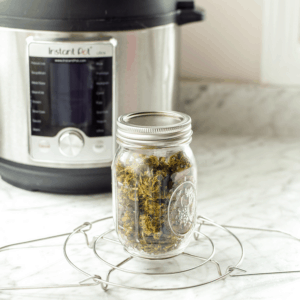A picture of a white counter top with an instant pot in the background focusing on a mason jar of cannabis flowers on a trivet