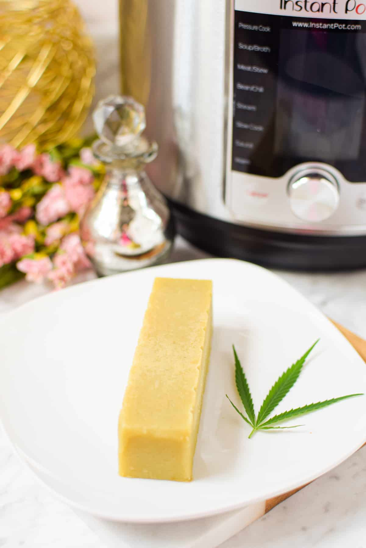 A picture of a stick of cannabutter on a white plate with an instant pot in the background